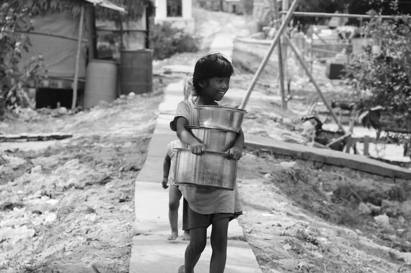 Girl carrying pots in an Indian village outside Yangon, Myanmar